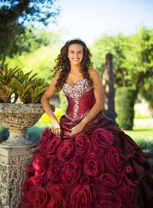Happy girl wearing her burgundy Quinceanera dress.