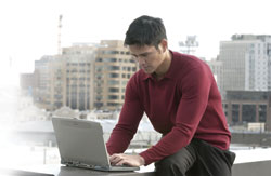 Man using online banking on his laptop while sitting along a river bank.