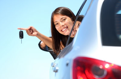 Young lady displaying keys from window of car